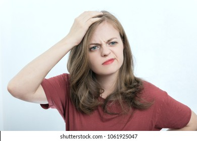 Portrait of blonde girl or young woman wearing red t-shirt with perplexed, puzzled, dumb, ignorant expression on her face scratching head with hand. When you don't know the answer