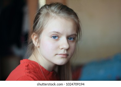 Portrait of a blonde hair blue eyes girl teenager at home