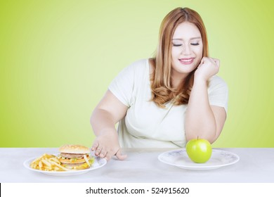 Portrait of blonde hair woman choosing a green apple rather than hamburger and french fries