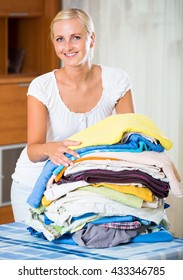Portrait of blonde housewife with stack of linen
