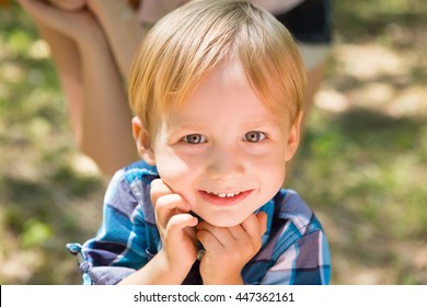 Portrait of blonde little boy posing outside