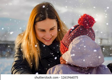portrait of blonde mother and child in hat looking from behind dressed in  winter clothes walking 715c5fd19554