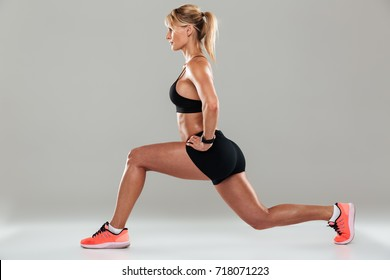 Portrait of a blonde muscular sportswoman doing boxing exercises isolated over gray background