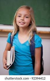 Portrait of a blonde schoolgirl holding her books in a classroom