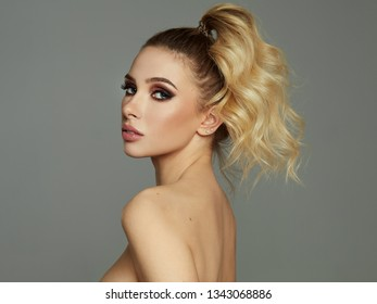 Portrait of blonde sexy woman isolated on gray background