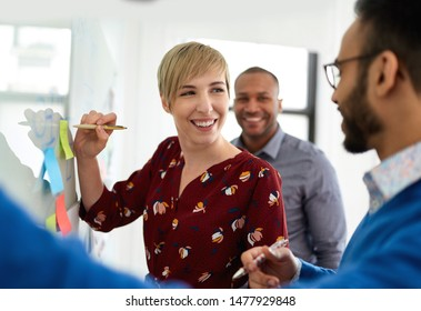 Portrait of a blonde short hair woman leading a diverse team of creative millennial coworkers in a startup brainstorming ideas