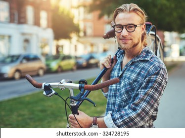 Portrait of blonde white man in the city with a bike