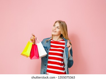 A portrait of a blonde who is amazed at the shopping that she has made over a  pink background.