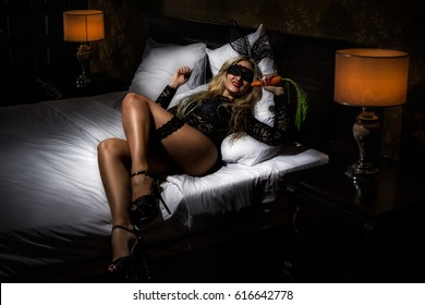 Portrait of blonde woman in black guipure lingerie lying on the bed with rabbit ears