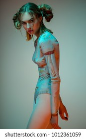 Portrait of blonde woman in blue bodysuit with mushrooms posing at camera