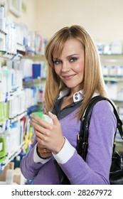 Portrait of blonde woman choosing shampoo in pharmacy.
