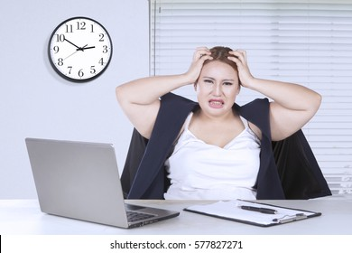 Portrait of blonde woman depressed with her job while holding her head in the office