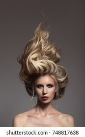Portrait of blonde woman. Hair storm on her head.