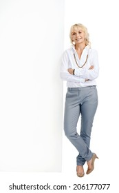Portrait of a blonde woman with her arms crossed smiling with copyspace