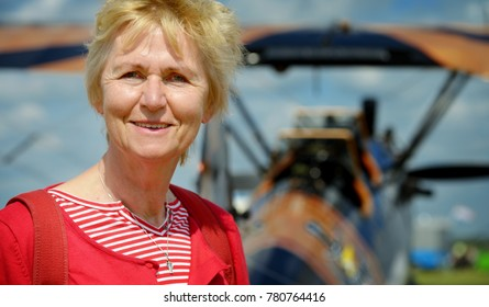 Portrait of a blonde woman in her fifties standing in front of a vintage biplane on an airport wearing  a red striped shirt on a hot and sunny day