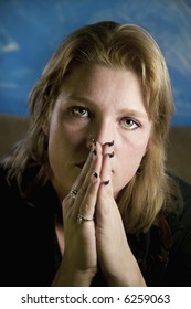 Portrait of a blonde woman with her hands folded in front of her face.