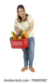 Portrait of a blonde woman holding a shopping cart full of fresh fruit and vegetables, isolated on white background