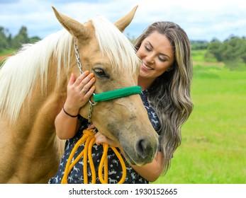 Portrait of blonde woman next to a horse, Ponta Grossa-Parana-Brasil - 01-21-2021