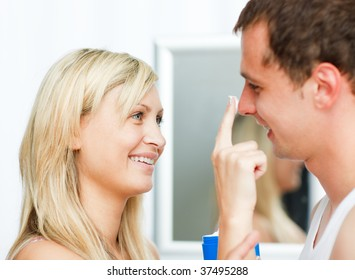 Portrait of a blonde woman putting cream on her boyfriend's nose in bathroom