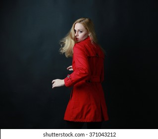 portrait of a blonde woman wearing red coat, turning to look at camera with hair flying in wind. dark background.