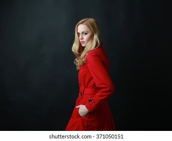 portrait of a blonde woman wearing red coat, looking over shoulder withhands in pocket. dark background.