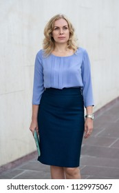 Portrait of a blonde woman wearing a skirt and blouse