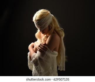 portrait of blonde woman wearing white lace dress and blindfold. back lit lighting against a black background.