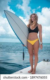 Portrait of blonde young woman in bikini with white surfboard and blue ocean on background in Maldives