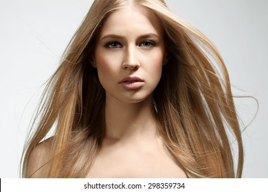 Portrait of a blonde young woman with flowing hair on a white background
