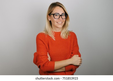 Portrait of blonde young woman with natural makeup and glasses in a red jersey posing against white background.