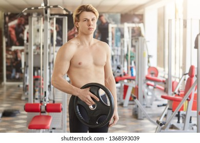 Portrait of blondy muscular sports guy standing in sport hall, holding black weight plate with one hand, having naked upper body, focused on result. Healthy lifestyle and physical trainings concept.