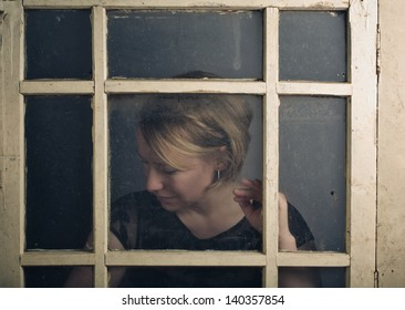 Portrait of a blone adult woman with old rustic Window
