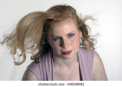 portrait of a blue eyed long haired redhead with hair blowing in wind and a white background