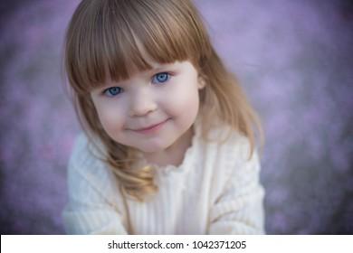 portrait of blue eyes baby girl smiling in vintage dress on violet fallen petals spring background