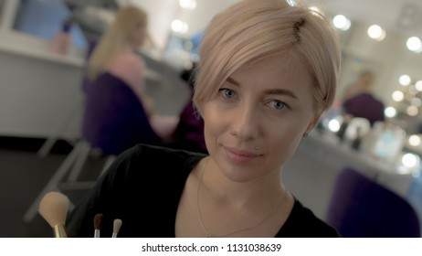 Portrait of blue-eyed blonde with short haircut looking at camera
