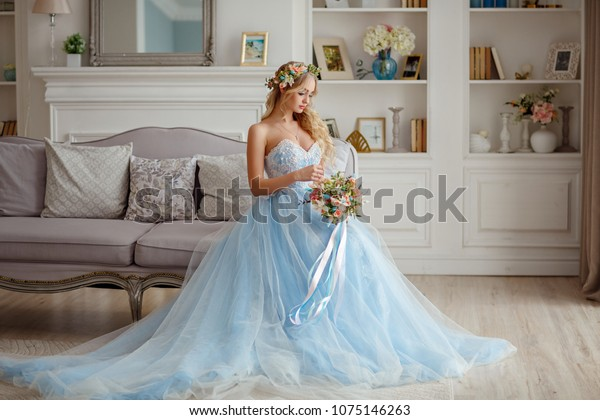 Portrait of a blue-eyed very beautiful blonde girl with a wreath of flowers on her head, in a blue bride dress