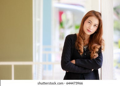 Portrait with blur background of long hair beautiful Asian woman in black sweater coat with smiling face in self-confidence posing