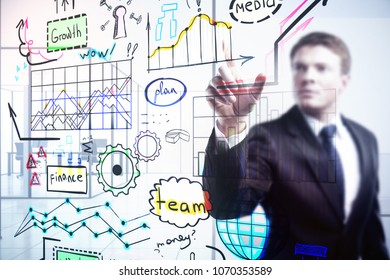 Portrait of blurry young businessman with business sketch. Leadership and growth concept