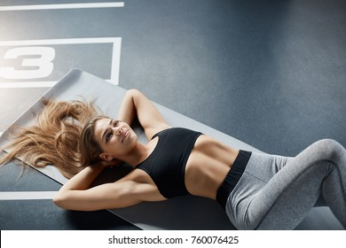 Portrait of body fitness trainer lady relaxing between exercise on gym mat with long hard spread. Dreaming about travelling.