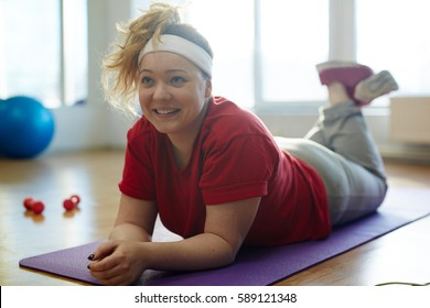 Portrait of body positive cute obese woman lying on yoga mat in fitness studio after working out and smiling happily in sunlight