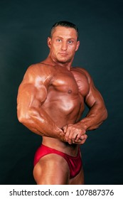 Portrait of bodybuilder posing on dark background.