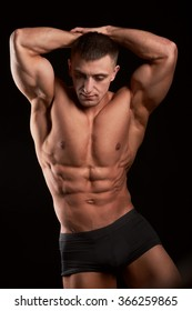Portrait of bodybuilder showing his abs.Studio shot.Isolated