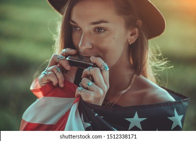 Portrait of boho chic woman in hat with american flag wearing silver rings with turquoise stone playes on harmonica outdoors. Jewelry indie girl with hippie style and boho fashion. Travel to america