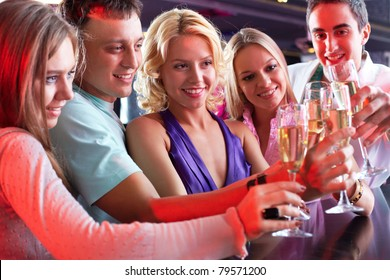 Portrait of boozing people in smart clothing toasting at party