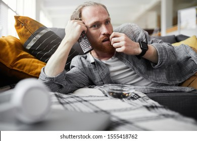 Portrait of bored bearded man watching TV while lying on couch in bachelors pad, copy space