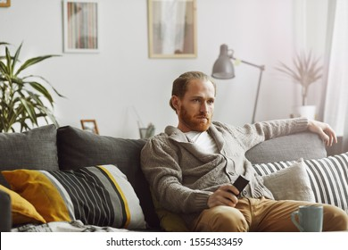 Portrait of bored bearded man watching TV at home and holding remote control while relaxing on comfortable couch, copy space