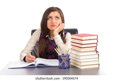 Portrait of  bored schoolgirl doing his homework at desk isolated over white background