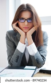 Portrait of a bored serious business woman working at her desk with paperwork