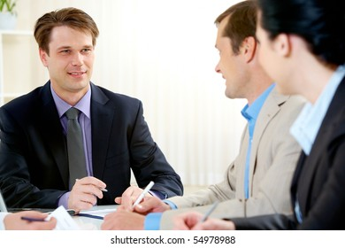 Portrait of boss explaining work to his colleagues