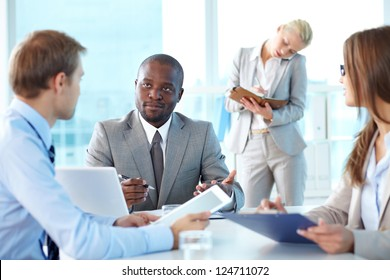Portrait of boss looking at his employee sitting near by
